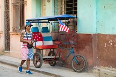 Pedicab, bikecab, velotaxi, cycle with flag of USA and seats , drivers shirt, cap, shorts with stars and stripes, Havana, Cuba..