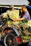 Pedicab driver and customer unload lemon grass.
