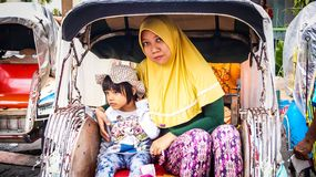 On a pedicab. Muslim mother with her daughter on a pedicab. Pedicab is unique transportation tools that still be used in some areas in Indonesia. This picture royalty free stock photos