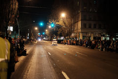 Pedicab zooms down empty downtown street, crowds lining both sid Royalty Free Stock Photo