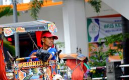 Pedicap Driver looking to front. With sharp look and look like thinking of something,  while resting in his pedicap or Becak. Bandung, Indonesia Royalty Free Stock Image
