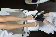 Pedicure στο πόδι γυναικών λάκκας στερεωτικών στιλβωτικής ουσίας καρφιών σαλονιών ομορφιάς Στοκ Φωτογραφία
