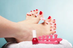 Pedicure ноги прикладывая красные toenails на сини Стоковые Изображения