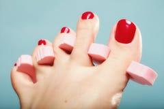 Pedicure ноги прикладывая красные toenails на сини Стоковые Фото