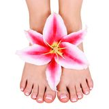 Pedicure. beautiful female feet with lily flower isolated Stock Photos