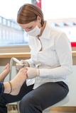 Pedicure caring for clients foot nails Royalty Free Stock Image