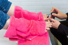 Pedicure chair spa and woman hands painting toes nail polish. After bath with pink towel Royalty Free Stock Photo