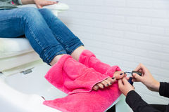Pedicure chair spa and woman hands painting toes nail polish Stock Photo