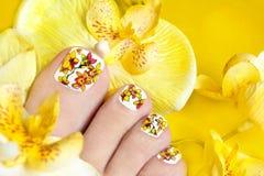 Pedicure con las orquídeas amarillas. Foto de archivo libre de regalías