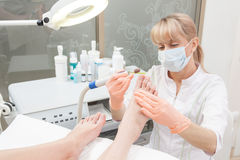 Pedicure in a Day Spa, feet nails. Woman receiving pedicure in a Day Spa, feet nails get cut and polish Royalty Free Stock Photos
