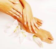 Pedicure del manicure con la fine del giglio del fiore su isolata su pe bianco Immagini Stock