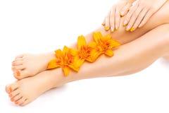 Pedicure en manicure met een oranje leliebloem Stock Afbeeldingen