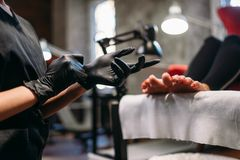 Pedicure master prepares for procedure with client stock photos