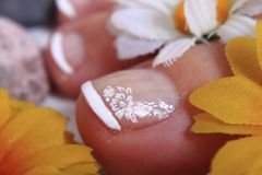 Pedicure nails, feet and flowers Royalty Free Stock Images