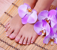 Pedicure with pink orchid flowers on bamboo mat Stock Photo
