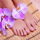 Pedicure with pink orchid flowers on bamboo mat Stock Images