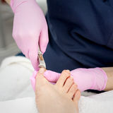 Pedicure in progress. A salon specialist makes pedicure for a young woman Royalty Free Stock Photography