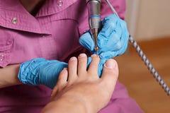 Pedicure Spa salon. Shaping nails and cuticles closeup. Stock Images