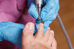 Pedicure Spa salon. Shaping nails and cuticles closeup. Royalty Free Stock Image