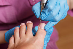Pedicure Spa salon. Shaping nails and cuticles. Hardware manicur Royalty Free Stock Photography