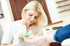 Pedicure specialist in beauty salon Stock Photography