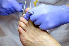 Pedicure specialist works with the patient Stock Images