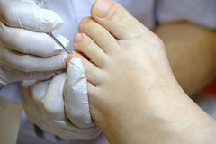 Pedicure specialist works with the patient Royalty Free Stock Photos