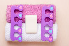 Pedicure, toe separators on towels. Foot care and cosmetics. Pedicure accessories set tools, two toe separators with bar soap on towels Royalty Free Stock Image
