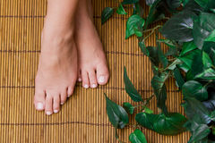 Pedicured feet on bamboo mat Royalty Free Stock Photos