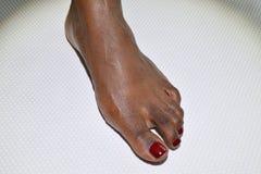 Pedicured kvinnlig fot på en vit yttersida fotografering för bildbyråer