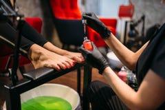Pedicurist делая косметическую процедуру, женский клиента стоковые изображения rf