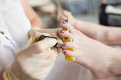 Pedicurist applying nail polish, close up photo.  Stock Image