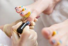 Pedicurist applying nail polish, close up photo.  Stock Images