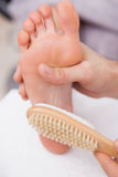 Pedicurist cleaning a customers foot Stock Photo