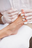Pedicurist cleaning a customers toe nails Stock Photos