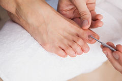 Pedicurist cleaning a customers toe nails Stock Image