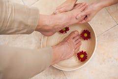 Pedicurist cleansing customer feet Royalty Free Stock Photo