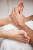 Pedicurist covering customers foot in soap Stock Images