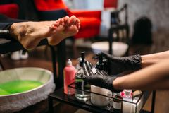 Pedicurist doing feet massage after pedicure bath royalty free stock images