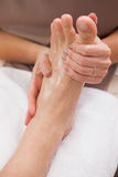 Pedicurist massaging customers foot Stock Photo