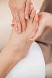 Pedicurist massaging customers foot Stock Images