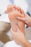 Pedicurist massaging customers foot Royalty Free Stock Images