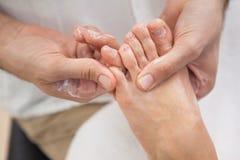 Pedicurist massaging customers foot Stock Photos