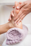 Pedicurist massaging a customers foot Royalty Free Stock Images