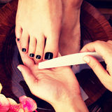 Pedicurist master makes pedicure on woman's legs Stock Photography