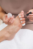 Pedicurist painting a customers nails Stock Photo
