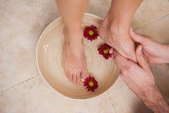 Pedicurist washing a customers feet Stock Photos