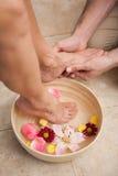 Pedicurist washing a customers feet Stock Photography