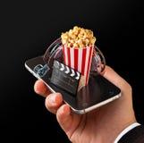 Pedido de Smartphone para bilhetes em linha do cinema da compra e do registro Filmes e vídeo de observação Live Fotografia de Stock