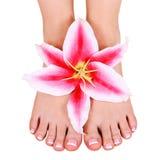 Pediküre. schöne weibliche Füße mit der Lilienblume lokalisiert Stockfotos